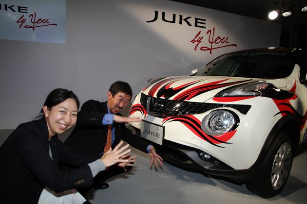 「JUKE by YOU」デカールデザインコンテスト グランプリ作品の前にて、日産自動車(株)商品広報部の若井さん(左)とジュークの歌舞伎顔をマネする志水さん(右)