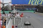 2009年度ドライバーズ・チャンピオンを決めたJ.バトンにチェッカーを降るF.マッサ(フェラーリ)